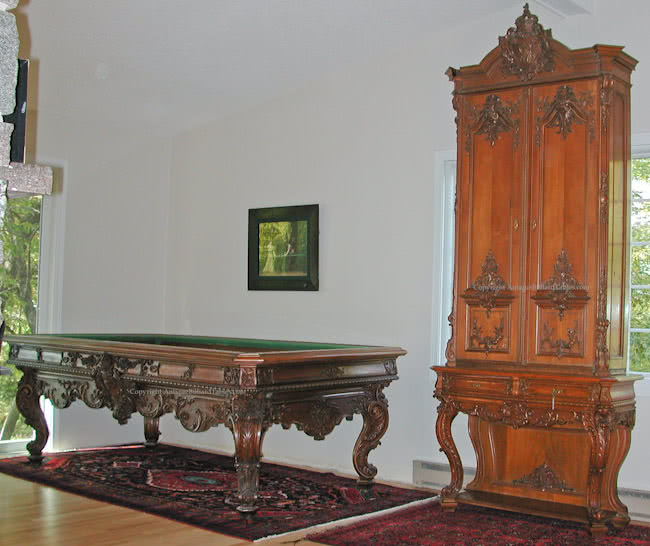 Antique Kaiser Wilhelm billiard table and cue cabinet in room